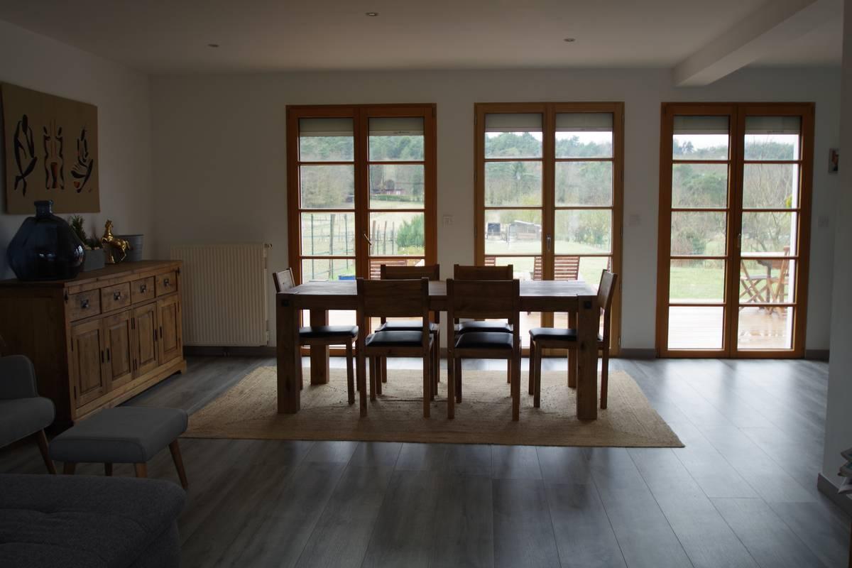 Salle à manger avec meuble en bois et table en chène centré sur un tapis de coco.