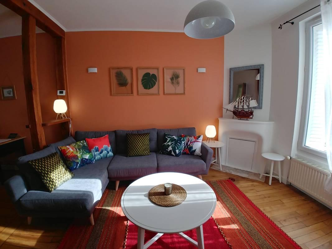 Canapé d'angle gris foncè dans un salon terracota et parquet en chene.