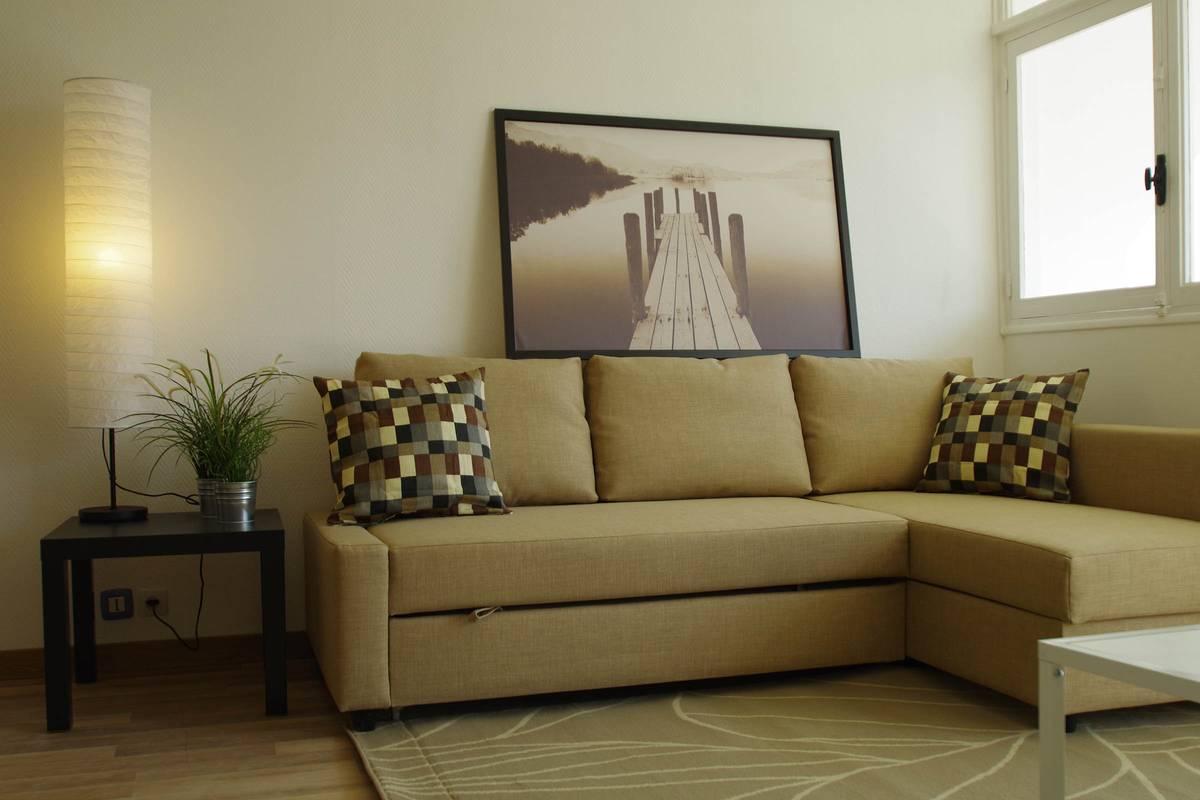 Canapé d'angle du salon au ton naturel dans une location meublée.