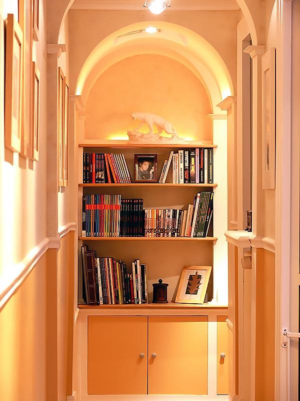 Mise en lumière de la bibliothèque en haut de l'escalier.