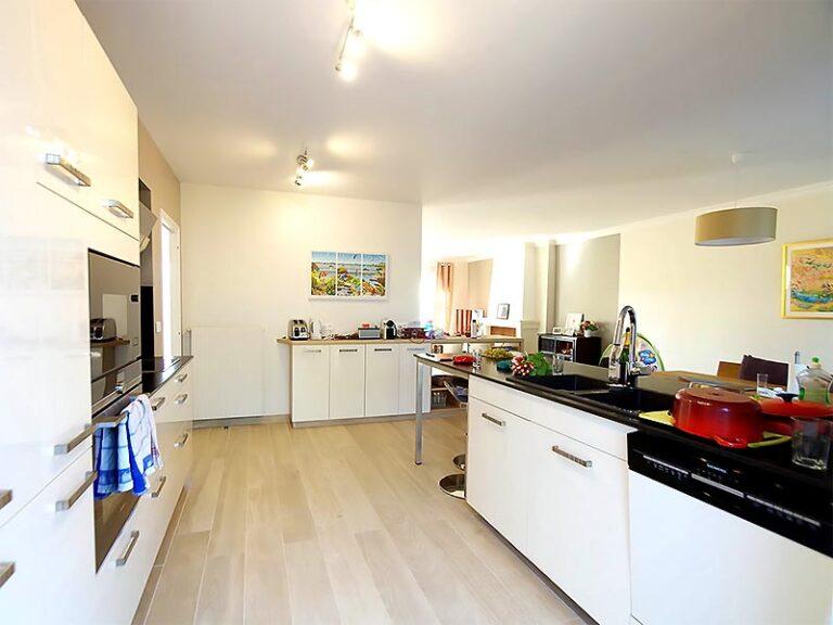 La cuisine au mobilier noir et blanc et son ilôt en épis dans lequel est intégré l'évier.