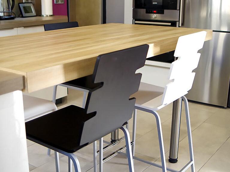 Table du coin repas en chêne naturel et chaises en noir et blanc.