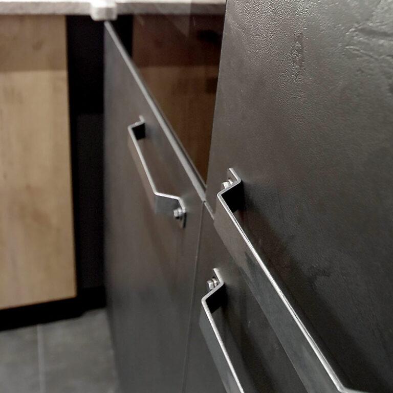 Détail des poignées en inox sur le mobilier en mélamine couleur béton ciré.