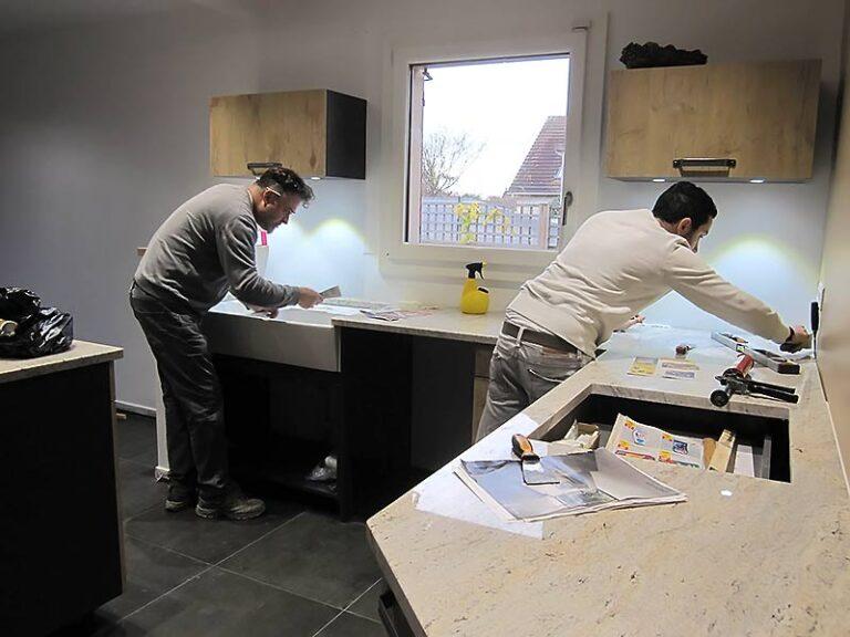 Ouvriers qui installent le plan de travail en granite