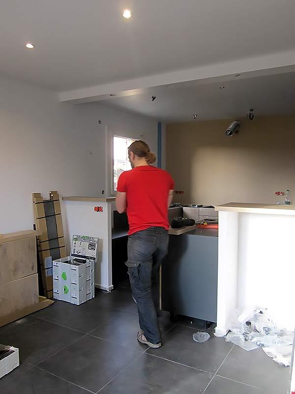 Menuisier en plein travail de pose du mobilier de cuisine